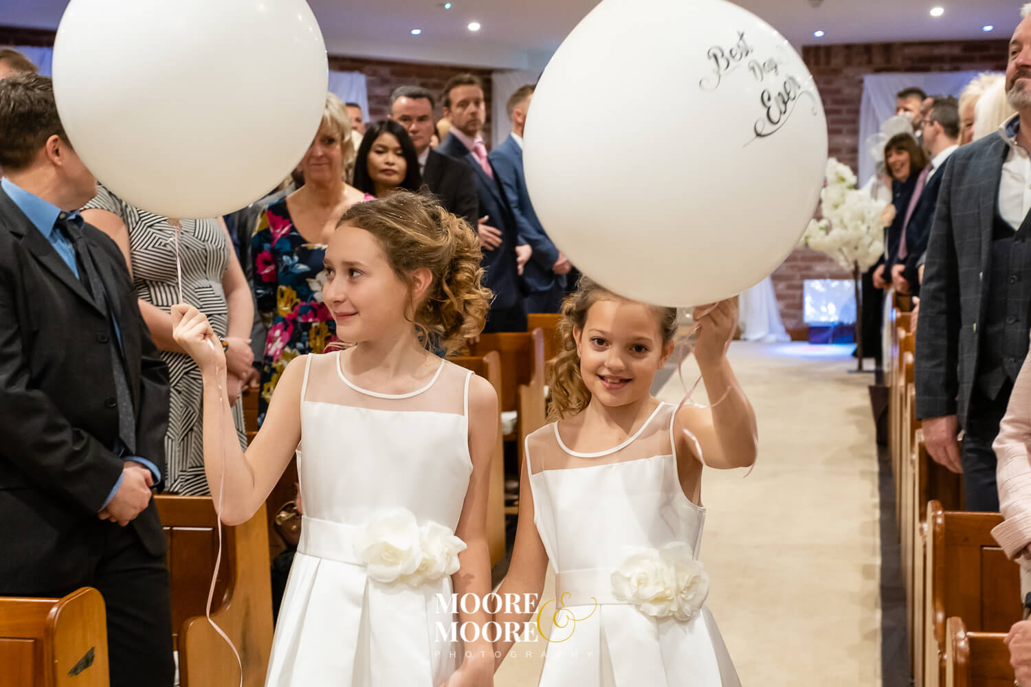 Young bridesmaids with balloons in aisle. Wedding Photos by Moore & Moore Photography, Hampshire