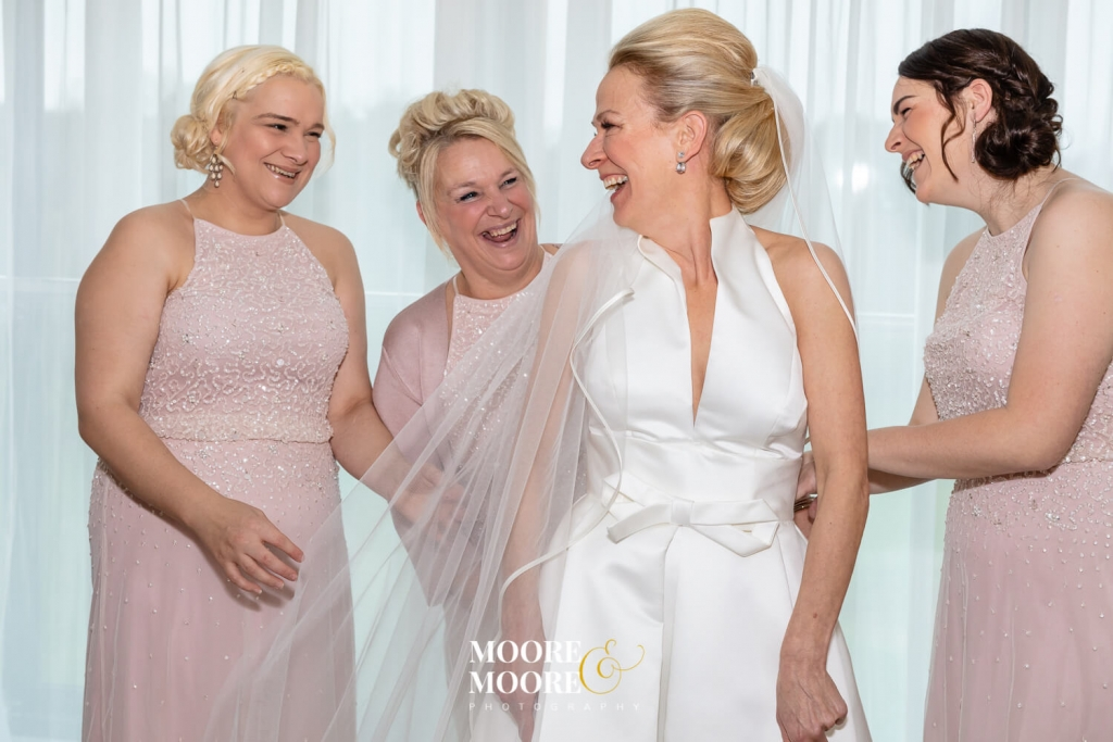 Bride and bridesmaids having fun. Wedding Photos by Moore & Moore Photography, Hampshire