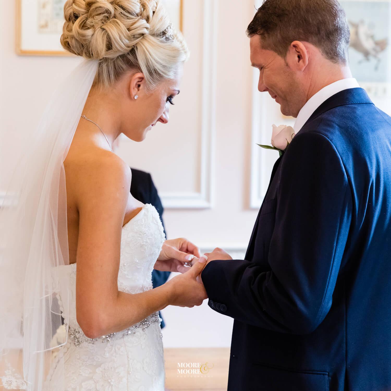 Exchanging wedding rings. Tylney Hall Wedding Photography by Moore & Moore Photography, Wedding Photographer Hampshire