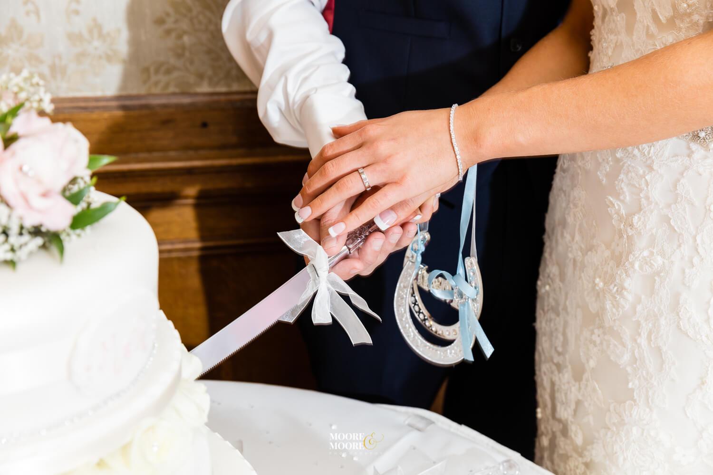 Cutting the cake. Tylney Hall Wedding Photography by Moore & Moore Photography, Wedding Photographer Hampshire